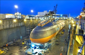 Black submarine with orange paint from cheatline down in drydock at nightfall. More details USS Ohio being converted from an SSBN to an SSGN in March 2004